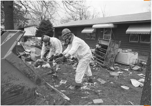 Two workers wearing gas masks and protective clothing loading debris contaminated by dioxin into tractor trailers. (©Bettmann/Corbis. Reproduced by permission.)