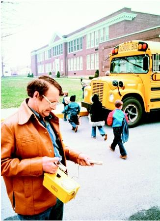 Acivil defense worker is using Geiger counter to check radiation level near a school building following the accidental radiation leak from the nearby Three Mile Island nuclear power plant. Schoolchildren are being evacuated via bus. (©Wally McNamee/Corbis. Reproduced by permission.)