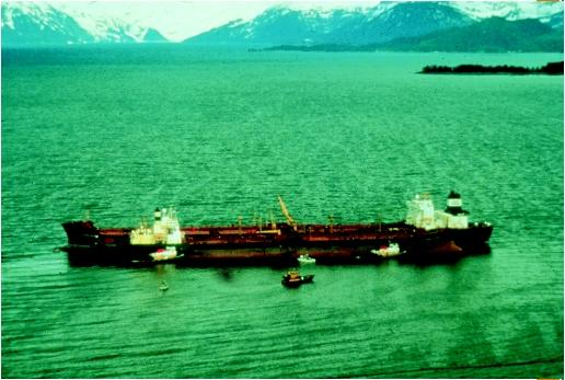 The Exxon Valdez leaking oil; the slick is visible along side of ship. (Courtesy of Richard Stapleton. Reproduced by permission.)