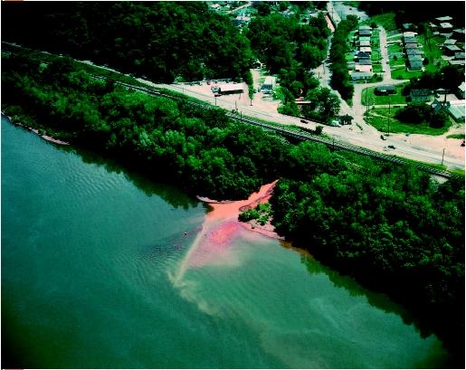 Aerial view of shoreline, showing a stream polluted with waste water runoff from strip mining flowing into the Ohio River. (© Charles E. Rotkin/Corbis. Reproduced by permission.)