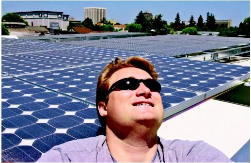 Eric Hassett, general manager of Palo Alto Hardware, standing next to solar panels on top of his store in California. (AP/Wide World Photos. Reproduced by permission.)