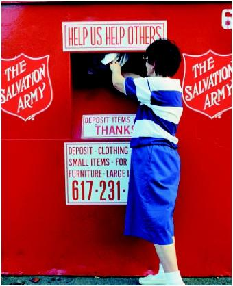 A woman donating clothes to the Salvation Army at a deposit drop-off site. (M. Stone, U.S. EPA. Reproduced by permission.)
