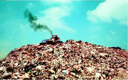 A bulldozer moving on top of a large mound of garbage. (United States Environmental Protection Agency. Reproduced by permission.)