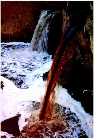 Liquid waste pouring from pipe into flowing river. (United States Environmental Protection Agency. Reproduced by permission.)