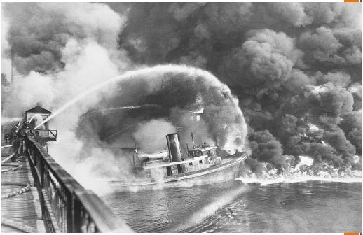 Firemen standing on a bridge over Cuyahoga River to spray water on the burning tug boat Arizona, which caused an oil slick at the Great Lakes Towing Company site, Cleveland, Ohio (November 3, 1952). (©Bettmann/Corbis. Reproduced by permission.)
